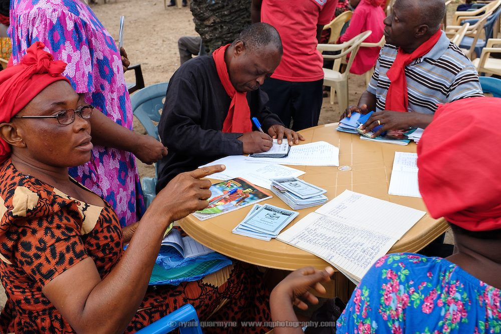 Dues are collected at a weekly early morning clan meeting in Ho in the Volta Region of Ghana. The clan is an important is an important part of the community's social fabric, and members pay dues to cover administration, funerals and other costs. The wearing of red signifies that the clan is in mourning - two of their number recently passed away, and funeral matters dominated the meeting.