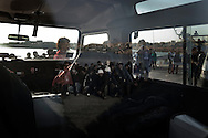 ITALY. Lampedusa:Tunisian migrants are reflected through a  window as they arrive in Lampedusa  on March  27, 2011. Copyright Christian Minelli.