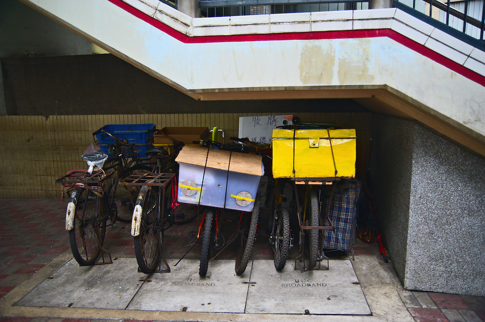 Bicycles with colorful containers parked under staircase, Hong Kong's Central district