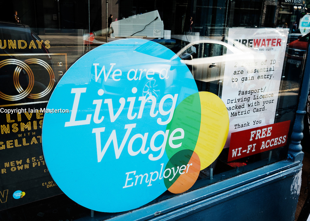 Sign in pub window stating that employees are paid a Living Wage in Glasgow, Scotland, United Kingdom