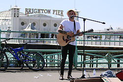 © Licensed to London News Pictures. 30/04/2015. Brighton, UK. A busker performs in front of Brighton Pier in a T-shirt while enjoying the warm weather, today Thursday April 30th 2015. Photo credit : Hugo Michiels/LNP