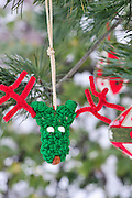 Funny green and red handmade reindeer Christmas ornament with pipe cleaner antlers and other red and white felt ornaments hang from the boughs of an Austrian pine tree (pinus nigra) outdoors with snow on the branches and copy space for a greeting card or other text. Vertical. Selective focus.