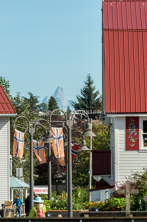 Devils thumb mountain is visible above Norwegian flags and red-roofed buildings in Petersburg, Alaska.