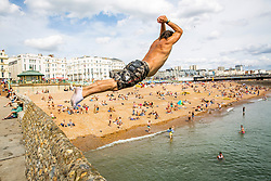 © Licensed to London News Pictures. 04/08/2016. Brighton, UK. Young men and boys cool off in the sea inn Brighton and Hove  as hot and sunny weather returns to the seaside resort. Photo credit: Hugo Michiels/LNP