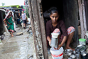 Mayuri Mahesh Pandit, 13, (centre) is washing dishes in front of her home, before leaving to participate at the Unicef-run 'Deepshikha Prerika' project inside the Milind Nagar Pipeline Area, an urban slum on the outskirts of Mumbai, Maharashtra, India, where she resides with her family.