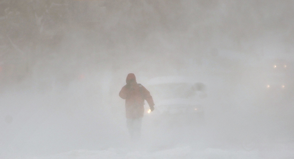 A pedestrian is seen walking down the middle of a street through in near white-out conditions during a major winter storm in Brooklyn, NY Sunday, 23 January 2005. The storm dumped over a foot of snow, over two in some places, on the Eastern United States, causing nearly 500 flights to be canceled Sunday morning at the New York metropolitan area's Newark, Kennedy and LaGuardia airports.