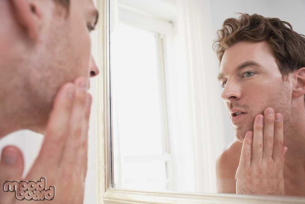 Man examining his stubble in mirror