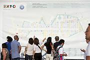 Visitors consult a large map of the exhibition site just entered in Expo 2015, Rho-Pero, June, 2015. &copy; Carlo Cerchioli<br /> <br /> Visitatori consultano una grande cartina del sito espositivo appena entrati a Expo 2015, Rho-Pero, giugno, 2015