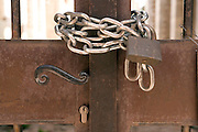 a metal gate locked with a chain and padlock