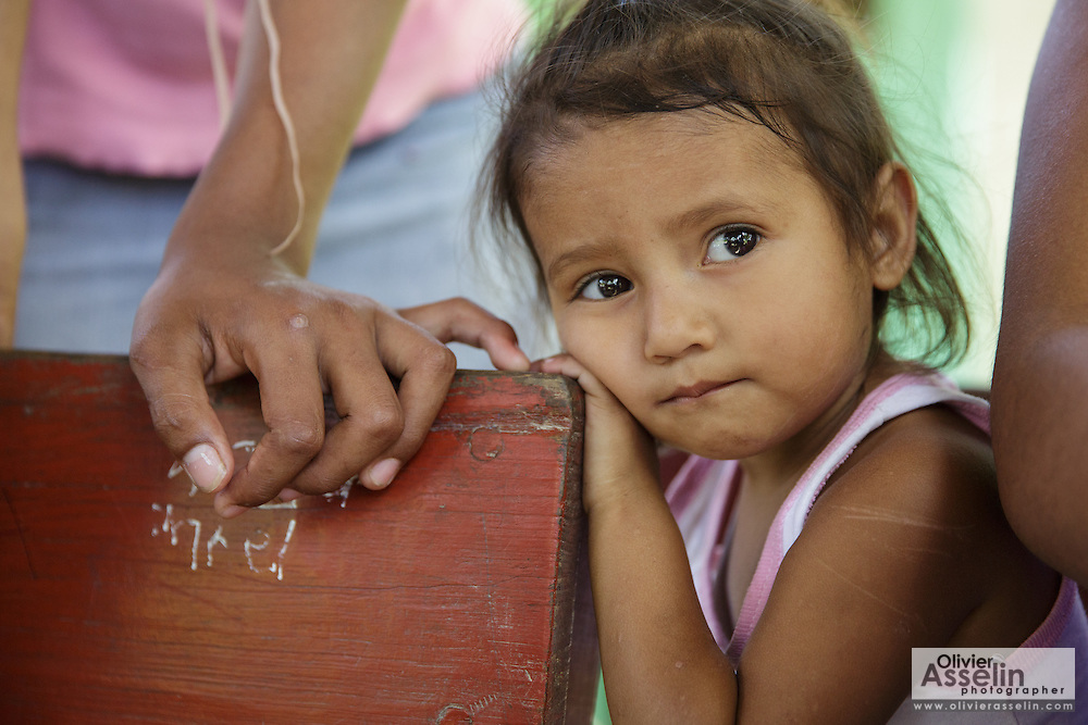 A young girl waits next to her mother during a vaccination session at the primary school in the town of Coyolito, Honduras on Wednesday April 24, 2013.