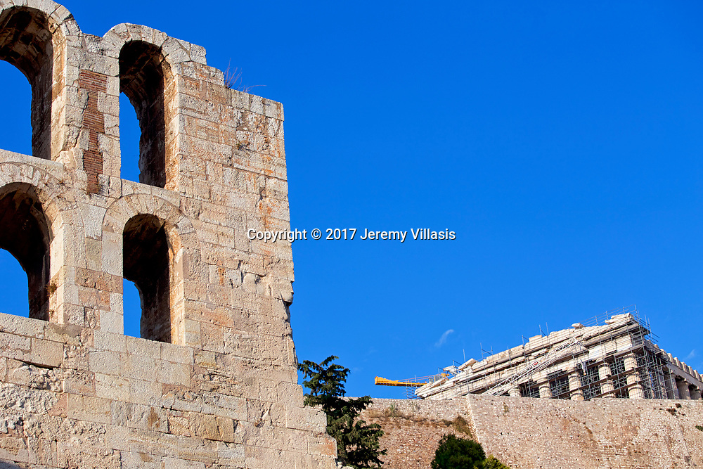 Section of the facade of the Odeon of Herodes Atticus on the southwest slope of the Acropolis of Athens with the Parthenon in the background.