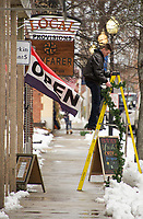 Nate Daubenspeck hangs garland from the light poles along Main Street Saturday afternoon hosted by Celebrate Laconia.  (Karen Bobotas/for the Laconia Daily Sun)