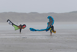 © Licensed to London News Pictures. 22/08/2020. Pembrey sands, Carmarthenshire, Wales, UK.Two kite surfers head for the water battling strong squall gusts of wind up to 35mph. Kite surfer enjoy the strong winds at Pembrey Sands in Carmarthenshire, Walse, UK.. Photo credit: Graham M. Lawrence/LNP