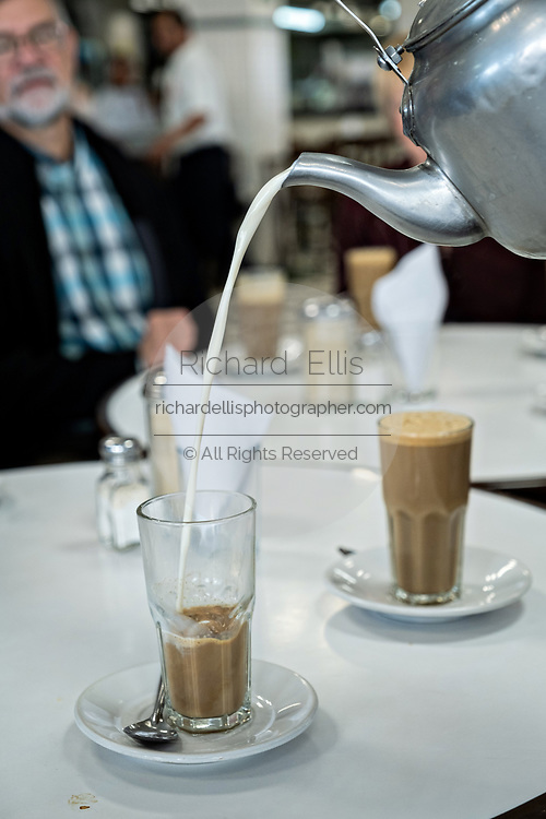 A waiter pours hot milk into coffee at the iconic Gran Café de La Parroquia along the Malecon in Veracruz City, Mexico. The cafe is known for their long pours of hot milky coffee known as a lechero which they have served since 1808 and in their current form has operated continuously since 1926.