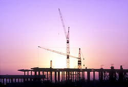 Stock photo of a silhouette of cranes at a large scale construction site at sunset.