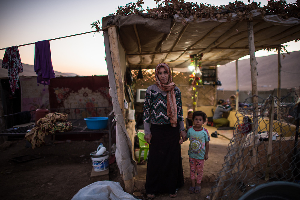 Ewaish* stands together with her daughter Mizgen* in front of her hut near Shingal City. ISIS kidnapped them in August 2014 and took them to Raqqa. Ewaish parents have been killed by ISIS when trying to flee and the remain of Ewaish's other ten year old daughter is unknown. Ewaish escaped her captors two weeks ago. She lives now with her husband and Mizgen in a provisional hut because her village is still in the hands of ISIS. (*names have been changed). Shingal (Sinjar), Iraq, August 27, 2015