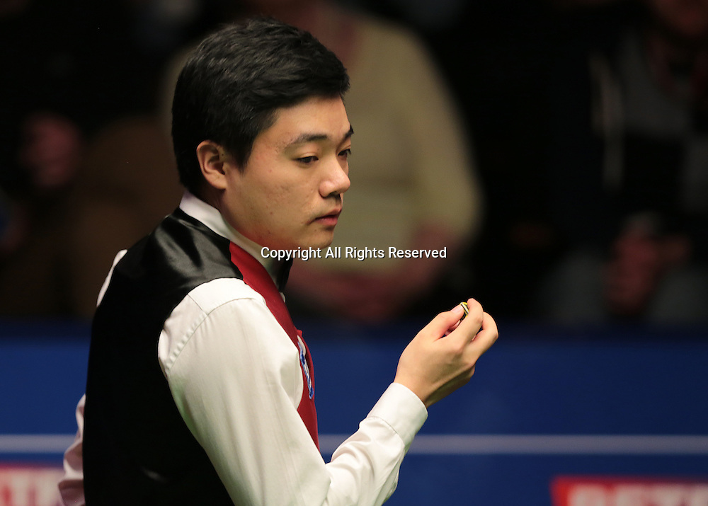 30.04.2016. The Crucible, Sheffield, England. World Snooker Championship. Semi Final, Ding Junhui versus Alan McManus.  Ding Junhui chalks his cue as makes his way round the table as he plans a shot ahead
