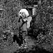 Family Home series, 6-8 years, Young, White, Boy, Outdoors, Garden, Posing, Fantasy, Fancy dress, White wig, Magic wand, Fairy wings, Stripe t-shirt, Shorts, Sandals, Happy, Smiling, Shouting, Summer, Black and white, Shadows, Plants, Climbers, Wooden door, England.