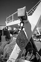 Carrucola arruginita appesa ad una paranza ormeggiata nel porto di Gallipoli (LE)