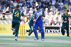 © Licensed to London News Pictures. 08/03/2012. Adelaide Oval, Australia. Brett lee celebrates the wicket of Kumar Sangakkara, as a dissapointed Sangakkara departs for 19 during the One Day International cricket match final between Australia Vs Sri Lanka. Photo credit : Asanka Brendon Ratnayake/LNP.