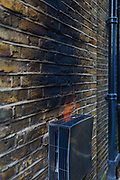 Flame emerging from a gas flue, with sooted and scorched brick wall of a house, blackened because of a faulty boiler, on 17th March 2017, in south London, England.
