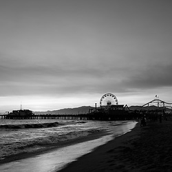 Santa Monica Pier beach sunset black and white photo along the Pacific Ocean. Santa Monica is a coastal beach city in Southern California in the United States. Copyright ⓒ 2017 Paul Velgos with All Rights Reserved.