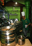 A koshary cook, preparing the cheapest meal you can get in Egypt. Rice, lentils, macaroni, browned onions, and tomato sauce are prepared separately, then spooned in layers on servings plates in this traditional Egyptian dished. You can get it as fast food.