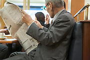 senior Asian businessman reading the economic section of a news paper in a coffee bar