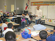 A community volunteer reads to Anderson ES students as part of the M.A.L.E. initiative.
