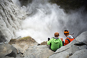 A couple sit overlooking the mighty Dettifoss waterfall in northern Iceland