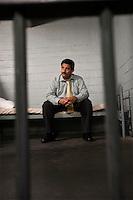 Criminal sitting on bed in jail