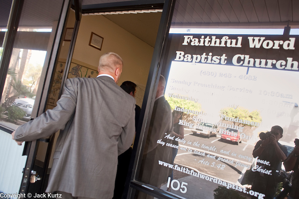 """Sept. 6, 2009 -- TEMPE, AZ: A congregant walks into the Faithful Word Baptist Church in Tempe, AZ, Sunday. Steven Anderson, the minister at the Faithful Word Baptist Church, an independent fundamentalist Baptist church, in Tempe has repeatedly said he hoped US President Barack Obama would die from a brain tumor and Sunday, Sept. 6, reiterated that he """"hates"""" President Obama. More than 200 people from a variety of liberal and progressive churches in the Phoenix area picketed Anderson's church Sunday morning, outnumbering his small congregation of about 50.  Photo by Jack Kurtz"""