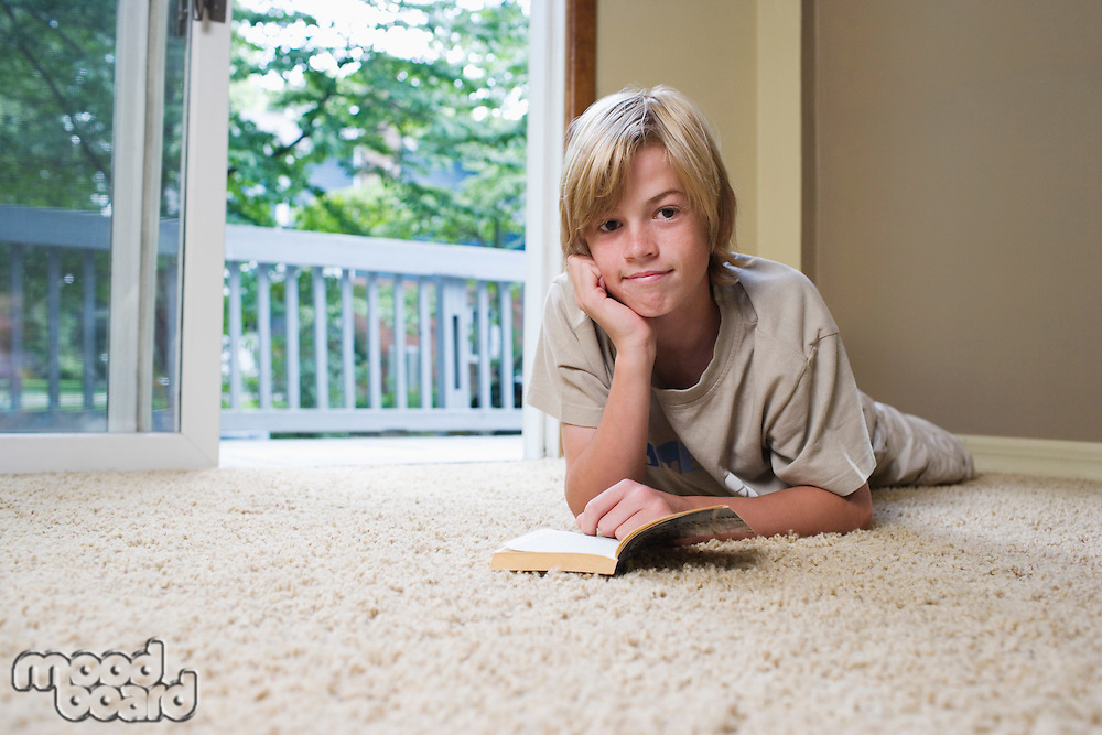 Portrait of boy (10-12) lying on carpet reading book