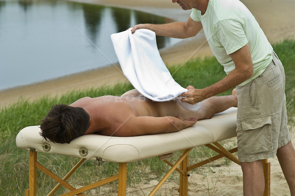 nude man getting a towel placed over him by a massage therapist outdoors.