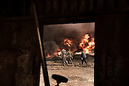 Iraq, Qayyara: Iraqi army fighters walks by a set on fire by IS crude oil field on October 2016. Alessio Romenzi