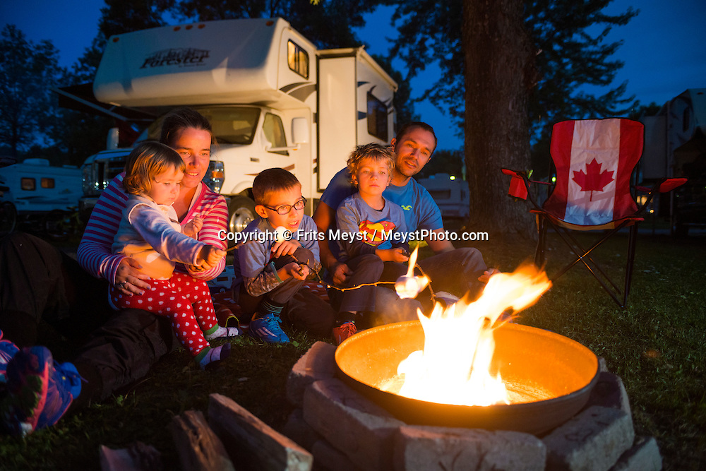 Quebec City, Quebec, Canada, August 2014. Grilling marshmellows over the campfire at the Quebec City KOA Camping. Quebec province is unique among North American tourist destinations. Its French heritage does not only set the province apart from most of its English speaking neighbors, it is also one of the few historical areas in North America to have fully preserved its Francophone culture. Its European feel and its history, culture and warmth have made Quebec a favourite tourist destination both nationally and internationally. Photo by Frits Meyst / MeystPhoto.com