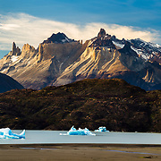 Hiker and Icebergs in Lago Grey in the Torres del Paine national Park, Patagonia, Chile.