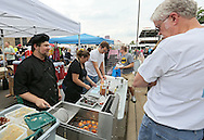 John Chargo (left), of Sweet Dee's Beignets, talks with customers as he fries beignets at the Downtown Farmers' Market in Cedar Rapids on Saturday morning, June 2, 2012. There were 244 vendors who participated in the first market of the year. (Stephen Mally/Freelance)