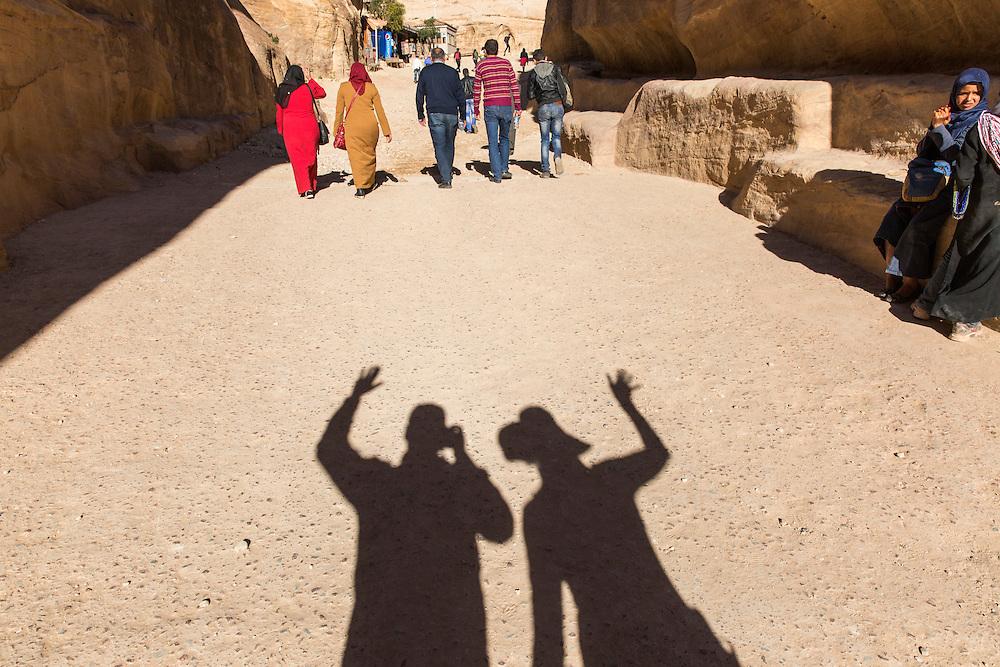 Jordan, Petra, Shadow cast by waving American tourists walking down path near Petra's ancient ruins