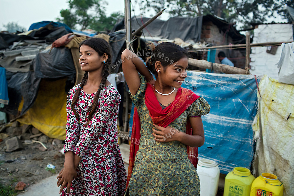Poonam, 13, (left) and her older sister Jyoti, 14, are standing in front of their newly built home in Oriya Basti, one of the water-contaminated colonies in Bhopal, central India, near the abandoned Union Carbide (now DOW Chemical) industrial complex, site of the infamous '1984 Gas Disaster'.