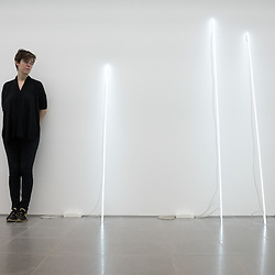 London, UK - 15 September 2014: a gallery assistant stands next to neon tubes of the 'Leaning Horizon' series during the press preview of the new exhibition by Cerith Wyn Evans at Serpentine Sackler Gallery.
