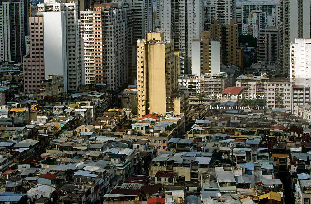 An aerial view of central Macau, looking down on high-rise apartments and poorer housing in this ex-Portuguese colony. ..Macau is now administered by China as a Special Economic Region (SER). Taken from a tall apartment block that overloooks the Rua do Almirant e Costa Cabral, we can view the tightly-packed cities of one of the most densely-populated connurbations in the world, this area is a packed warren of houses, businesses and tower blocks, home to a population of mainland 95% Chinese, primarily Cantonese, Fujianese as well as some Hakka, Shanghainese and overseas Chinese immigrants from Southeast Asia and elsewhere. The remainder are of Portuguese or mixed Chinese-Portuguese ancestry, the so-called Macanese, as well as several thousand Filipino and Thai nationals. The official languages are Portuguese and Chinese. The Macau Special Administrative Region, more commonly known as Macau or Macao is one of the two special administrative regions (SARs) of the People's Republic of China (PRC), along with Hong Kong. Administered by Portugal until 1999, it was the oldest European colony in China, dating back to the 16th century. The administrative power over Macau was transferred to the People's Republic of China (PRC) in 1999, 2 years after Hong Kong's own handover. Macao's gambling revenue in 2006 weighed in at a massive £3.6bn - about £100m more than Las Vegas.
