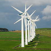A row of electrical generating wind turbines in a wind farm on the top of the English Pennine Hills in Britain.