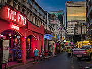 "26 MAY 2016 - BANGKOK, THAILAND: A woman walks past the ""Pink Panther,"" one of the bars in the Patpong adult entertainment district in Bangkok.          PHOTO BY JACK KURTZ"
