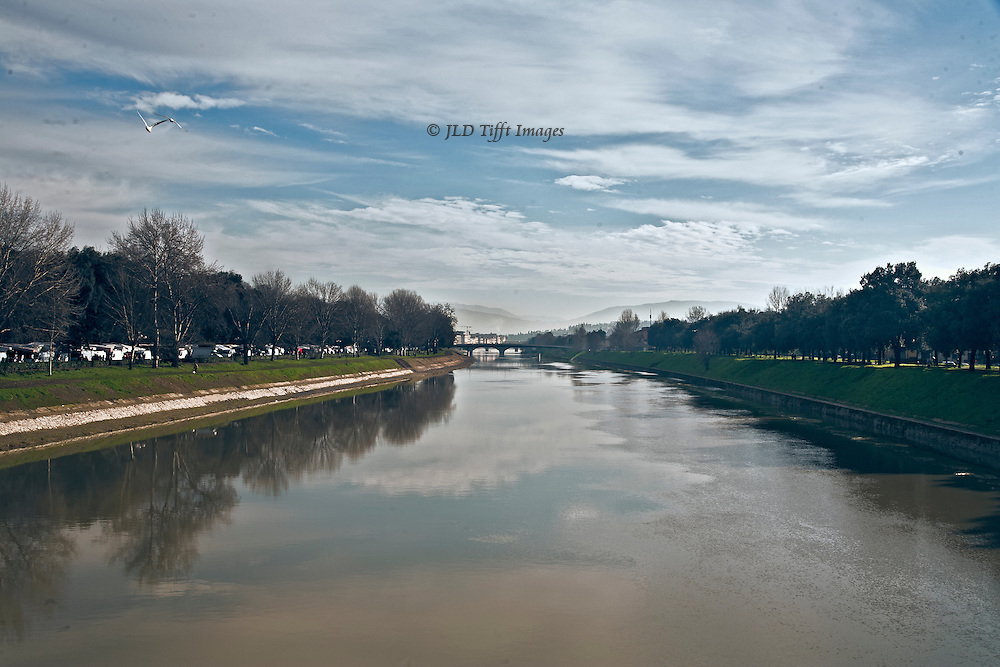 Arno River at Cascine, outside Florence.  Weekly market stalls just visible at left.