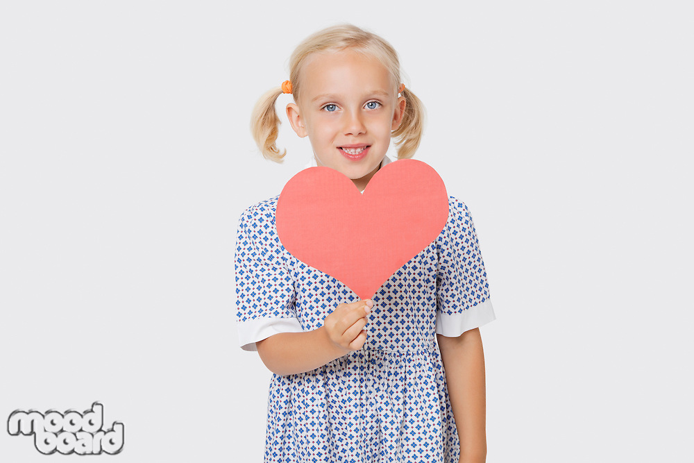 Portrait of a happy young girl holding pink paper heart over white background