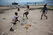 CLIENT: CBM<br /> <br /> Sebastien, 10, plays goalie during a soccer game with friends and cousins along the waterfront in the tent camp where he lives in the Carrefour neighborhood of Port-au-Prince, Haiti.  His mother was killed and his leg crushed in the January 12 earthquake.
