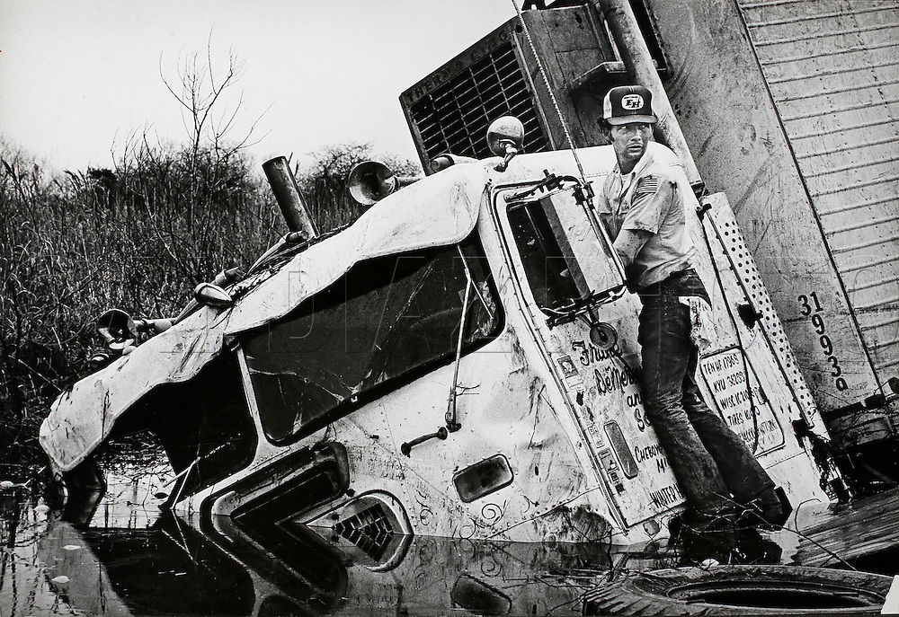 Vince Perkins attempts to salvage his semi-trailer truck and 1,000 crates of oranges stuck in mud and water along Paynes Prairie Preserve, South of Gainesville, Florida, in 1982.