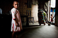 As her daughter, Mahfuza Akhter (5) looks on, Shahida Begum, 35, goes about her daily household chores in her hut in Palashbari Villlage, Taragonj, Rangpur, Bangladesh on 18th September 2011, after a regular day of work as a saleswoman earning 3500 - 5000 Bangladeshi Taka per month. She is one of many rural Bangladeshi women trained by NGO CARE Bangladesh as part of their project on empowering women in this traditionally patriarchal society. Named 'Aparajitas', which means 'women who never accept defeat', these women are trained to sell products in their villages and others around them from door-to-door, bringing global products from brands such as BATA, Unilever and GDFL to the most remote of villages, and bringing social and financial empowerment to themselves.  Photo by Suzanne Lee for The Guardian