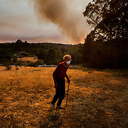 Vete Navokowski, 93, walks across his property in Fallbrook, California as a fire at Camp Pendleton burns in the background, May 15, 2014.  Whipped by the wind, flames swept over the parched land close to homes and roads in nine fires across the county, with black smoke filling the sky as California entered the height of wildfire season in the midst of one of the state's worst droughts. No major injuries were reported.  REUTERS/Sam Hodgson   (UNITED STATES)